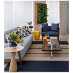 Modern Living Room, Blue Brown Striped Rug, Blue Sofa, Blue Chair, Wooden Coffee Table, Wooden Side Table, Brown Brick Wall, Vertical Plants, Yellow Stool
