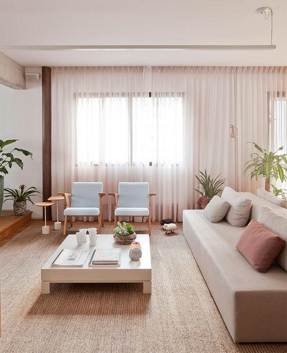 modern living room, brown rattan rug, wooden floor, pale sofa, soft blue chair, white low wooden coffee table, side table