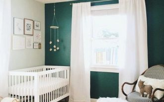 nursery, green wall, white wall, white curtain, rattan rug, white wooden crib, rattan basket, rattan chairs with stool with fur cushion