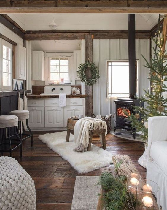 open tichen, wooden floor, white wall, white kitchen cabinet with wooden top, white sink, window table, wooden bench, black metal fireplace, white sofa, white ottoman
