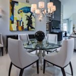 Pedestal Dining Table With Leaf Artwork Chandelier Glass Table White Dining Chairs White Flooring Gray Wall Wall Sconces