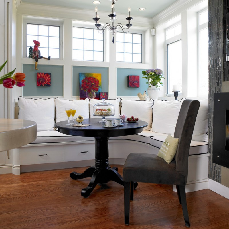 pedestal dining table with leaf glass windows fireplace wooden floor black chair white curved window bench drawers white pillows floral artworks