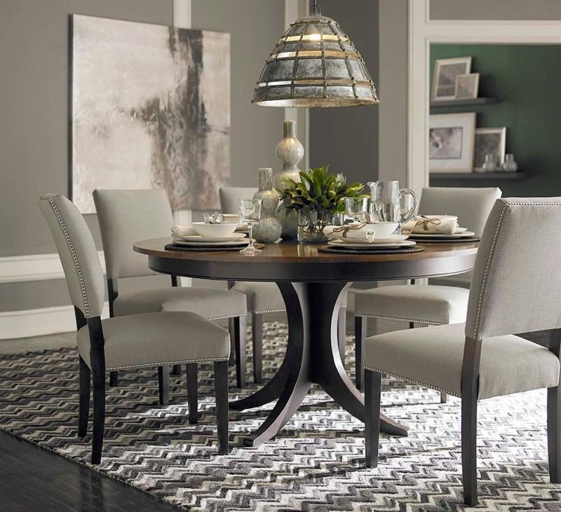 pedestal dining table with leaf pendant lamp gray herringbone rug black flooring gray chairs gray walls artwork white wall trim