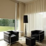 Privacy Window Treatment Black Leathered Armchairs Black Leathered Ottoman Persian Area Rug Sheer Curtain Wide Glass Windows Black Floor Lamp Glass Side Table