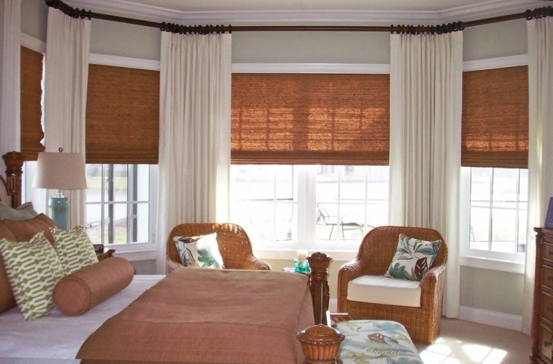 privacy window treatment woven shades white drapes glass windows gray walls rattan armchairs brown and white bedding bench wooden dresser table lamp