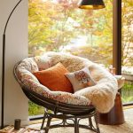 Rattan Frame With Flowery Cushion, Fur Blanket, Floor Lamp, Rattan Rug, Side Table