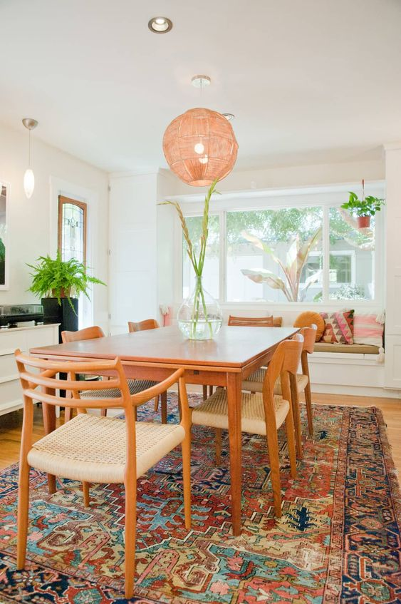 rose round pendant, white ceiling, white wall, wooden floor, warm colored rug, wooden table, wooden chairs, white window nook with pillows
