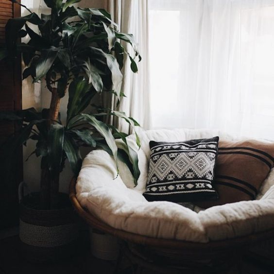 round rattan chair with white cushion, pillows, plants, window with white curtain