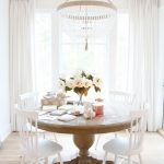Round Wooden Dining Table, White Wooden Chairs, Chandelier, White Ceiling, Wooden Floor, White Curtain