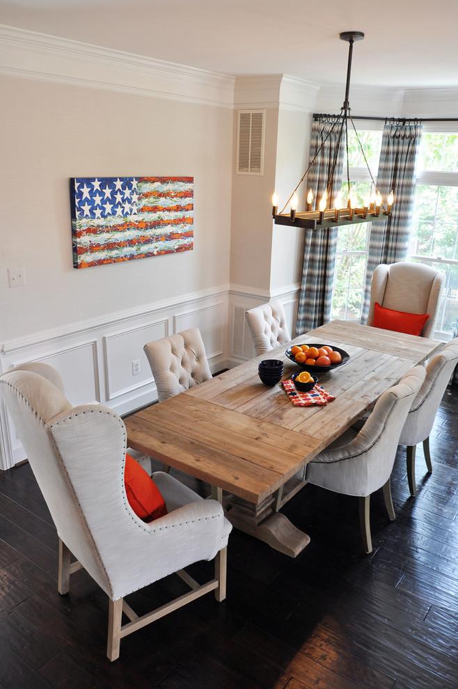 rustic dining table chandelier dark flooring beige tufted chairs glass wiindows decorative curtains white trim orange pillows artwork