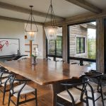 Rustic Dining Table Glass Pendant Lamps Artwork Black Console Table Black Chairs Wooden Floor Wood Beams Glass Windows Rug