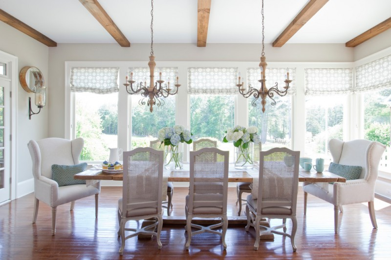 rustic dining table white windows white wingback chairs white chairs chandeliers wooden floor wall mirror wall sconces decorative shades glass door flower vases