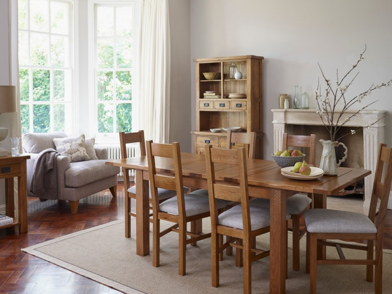 rustic dining table wooden cupboard area rug wooden floor fireplace wooden chairs gray armchair windows table lamp white curtains