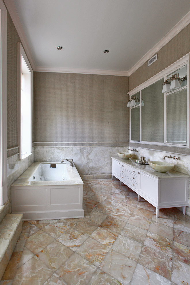sink bowl beige marble floor tile white built in bathtub brown wall large wall mirrors white wall sconces white low vanity window wall mounted faucet