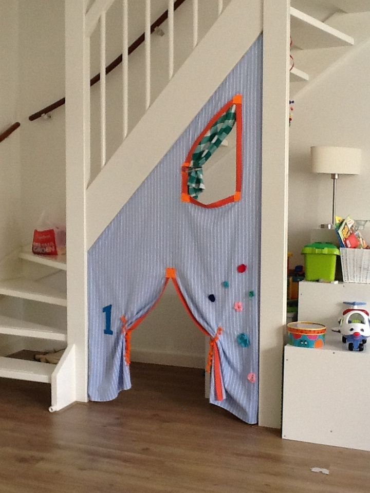 small alcove, wooden floor, under the stairs, fabric curtain, hole for window