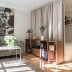 Small Apartment, Wooden Floor, Low Wooden Shelves, Grey Sofa, Grey Rug, Coffee Table, Floating Shelves, Fabric Curtain