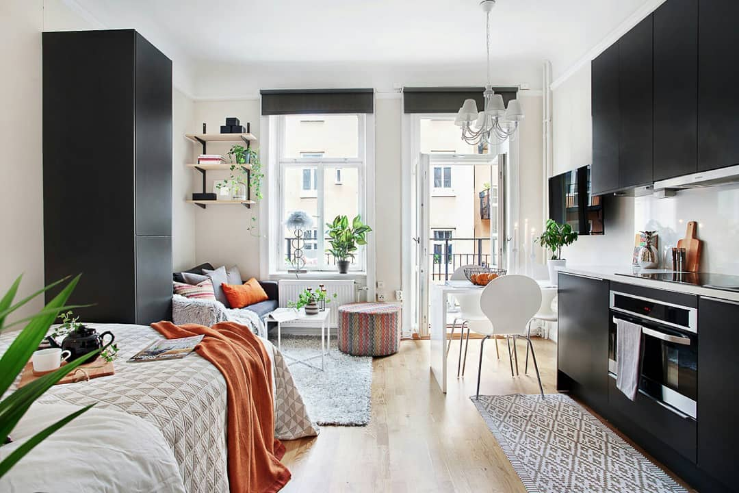 small apartment, wooden floor, white dining set, black upper bottom kitchen cabinet, black cupboard, black sofa, floating shelves, bed, white chandelier