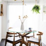 Small Dining Room, Wooden Floor, White Wall, Golden Bulb Chandelier, White Vase, Clear Glass Round Table, Wooden Chairs With Black Seat