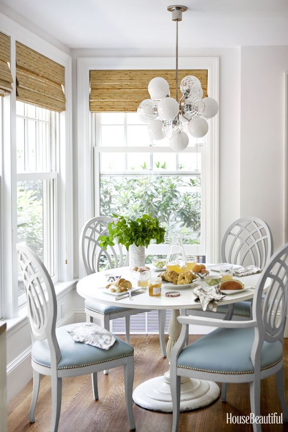 small dining set with round table, white wooden chairs with blue seating, white wall, rattan shade, white pendants, wooden floor