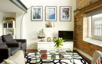 small living room design ideas black armchair tan sofa pillows glass coffee table window brick wall white console floor lamp