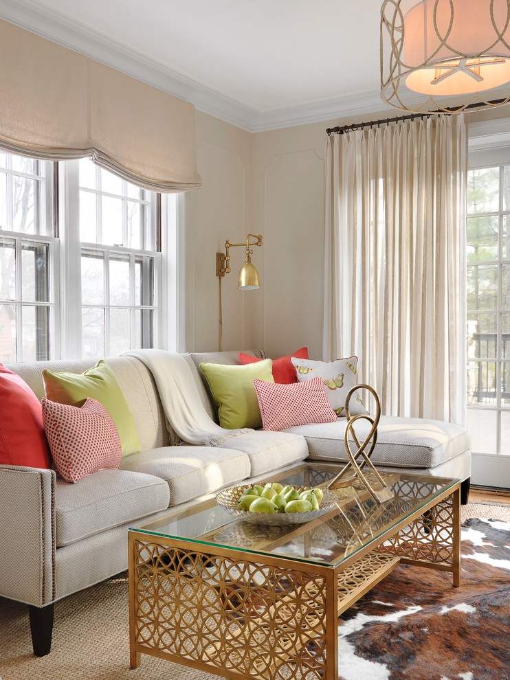 small living room design ideas gold wall sconces gold and glass coffee table cow hide rug gray sectional sofa colorful pillows beige shade and curtains windows