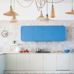 Some Rattan Pendants With Different Shape, White Textured Kitchen, White Wall, White Bottom Cabinet, Patterned Floor, Blue Upper Cabinet