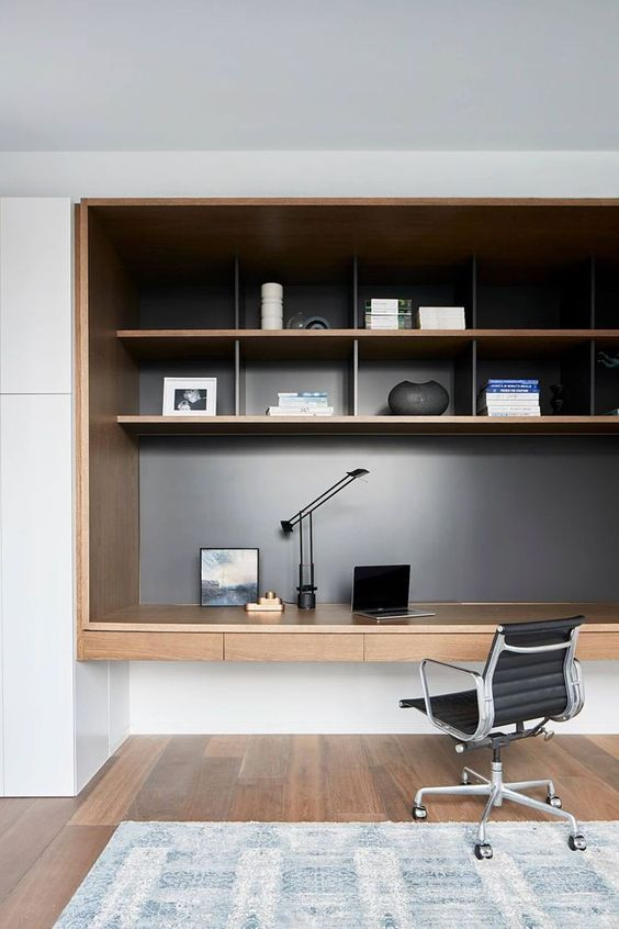 study in alcove with wooden box, wooden shelves inside, drawers at the bottom, black office chair