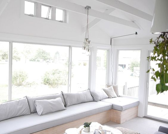 sun room, grey floor, wooden bench with grey cushion, pillows, white wall, pendant