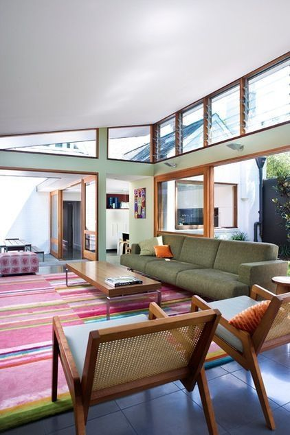 sun room, grey tiles, colorful rug, green sofa, wooden coffee table, wooden chairs with blue cushion, sloping ceiling