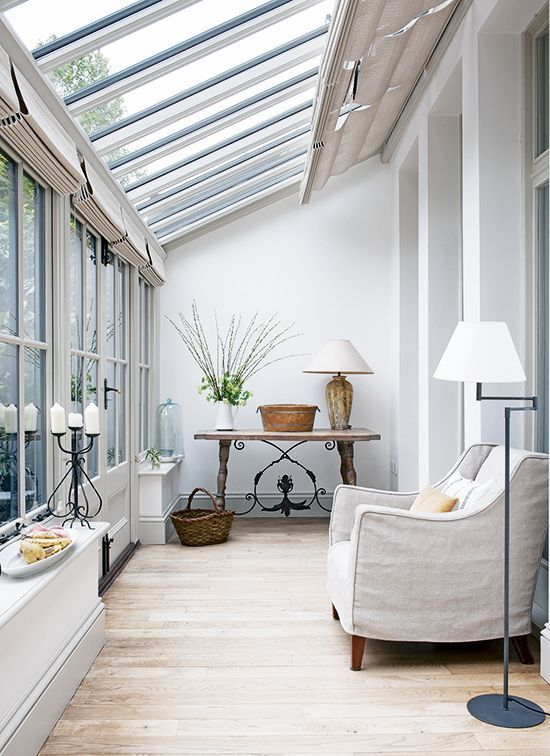 sun room, wooden floor, white wall, glass wall and ceiling, shades, white chair, floor lamp, long side table, table lamp