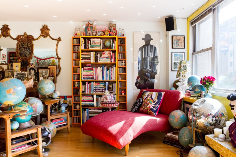 unique bookcase antique wall mirrors windows shades globes wooden floor red lounge chairs white yellow walls side table