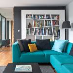 Unique Bookcase Blue Sectional Sofa Black Coffee Table Glass Windows Gray Textured Area Rug Black Floor Lamp Colorful Pillows