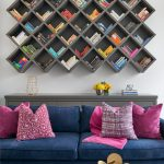 Unique Bookcase Gray Wall Mounted Bookcase Gray Console Table Blue Sofa Pink Pillows Blue Velvet Ottoman White Walls