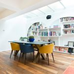 Unique Bookcase White Walls Skylight Wooden Floor Wooden Dining Table Blue And Yellow Chairs Brown Cabinet Built In Ovens Rug