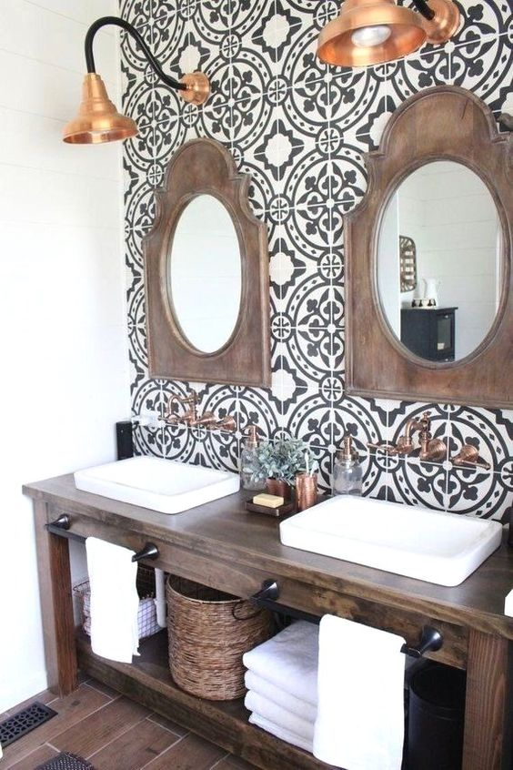 vanity with patterned tiles on the wall, wooden table, mirror with wooden frame, copper pendant, brown floor tiles