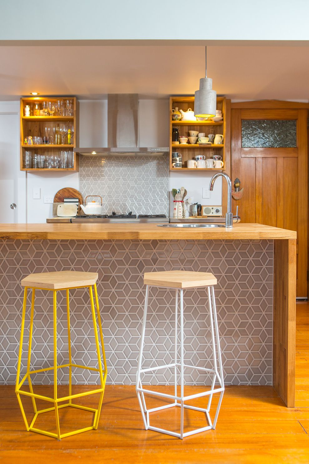 warm kitchen, wooden floor, wooden island top, hexagonal tiles under the island, geometric stool with wooden top, grey backsplash, white wall, wooden floating shelves