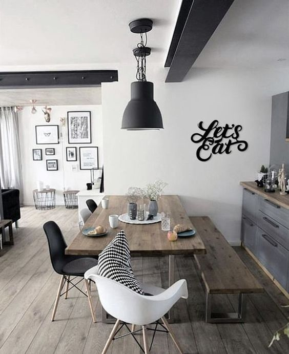 white and black mid century modern chairs, wooden rectangular table, wooden long bench, black pendant, white wall, grey bottom cabinet with wooden kitchen top
