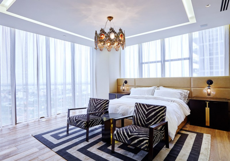 white bedroom decorating ideas antique chandelier black and beige rug black armchairs beige headboard glass wall sconces windows white curtains white bedding