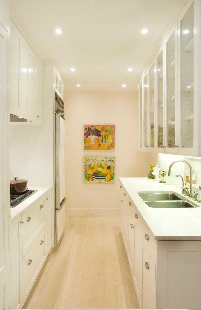 white cabinet with glass door artwork double sink faucet backsplash white countertop stovetop drawers range hood refrigerator