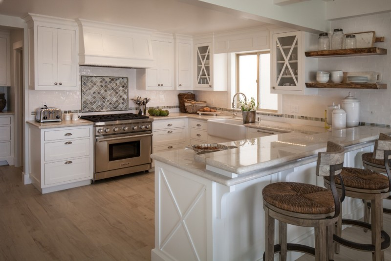 white cabinet with glass door wooden barstools white countertop windows wooden shelves wooden floor oven stove farmhouse sink