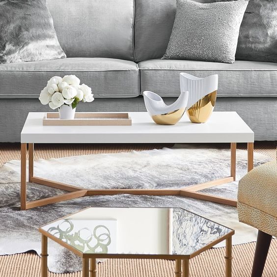 white coffee table with copper legs, white rug, beige rug, grey sofa, glass hexagonal table