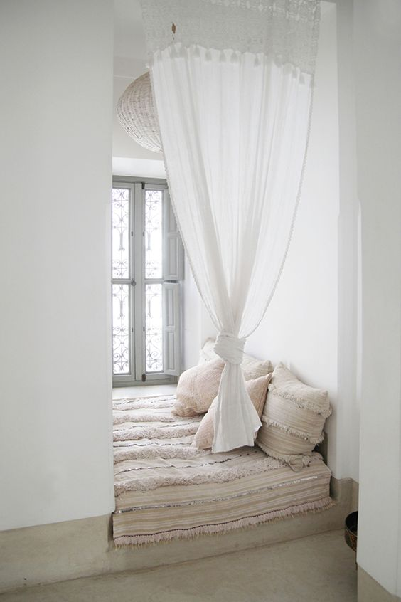 white dented nook with small windows, curtain, chandelier, cushion, pillows