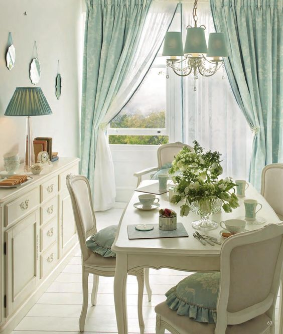 white dining table, white chairs, white wooden floor, white wall, white classy cabinet, blue chandelier, blue curtain