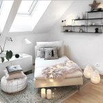 White Lounge Chair Under Sloping Ceiling With Glass Window, White Low Cabinet, White Round Ottoman, Rug, Floating Shelves