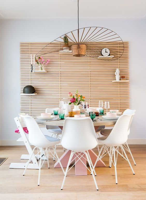 white mid century modern chairs, round wooden table with pink legs, wooden slat wall, white wall, wooden floor, large pendant
