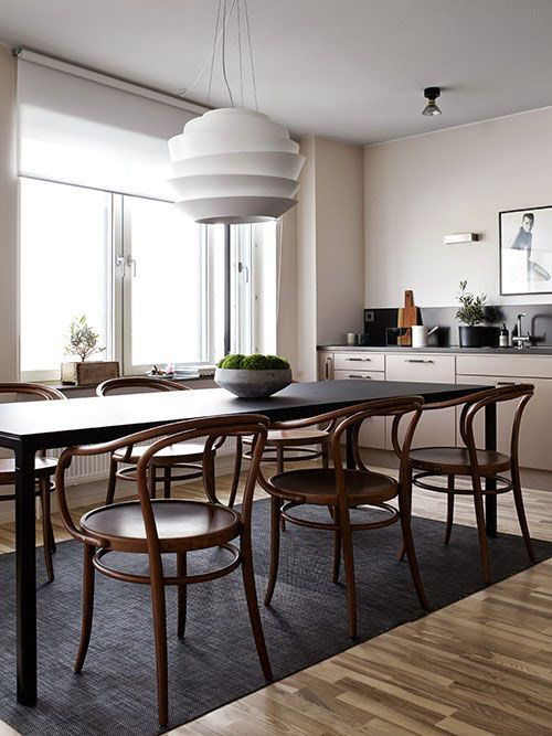 white modern pendant, beige wall, beige ceiling, wooden floor, black wooden table, wooden chairs,