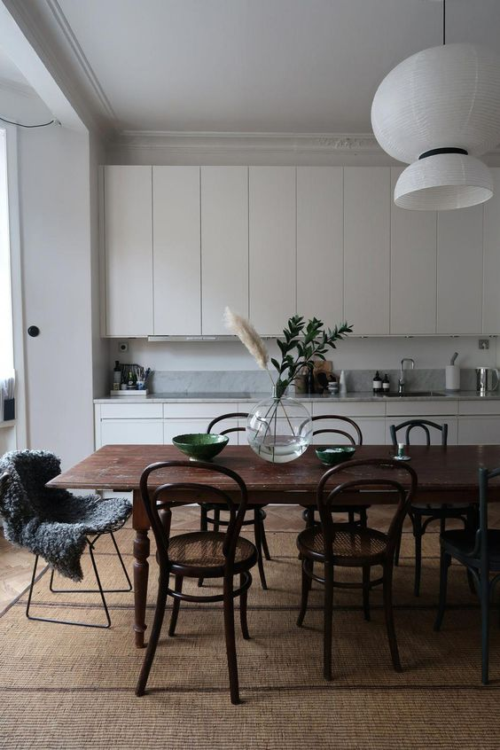 white modern pendant, white wooden top cabinet, white wooden bottom cabinet, white grey backsplash, wooden dining table, dark wooden chairs with rattan seating
