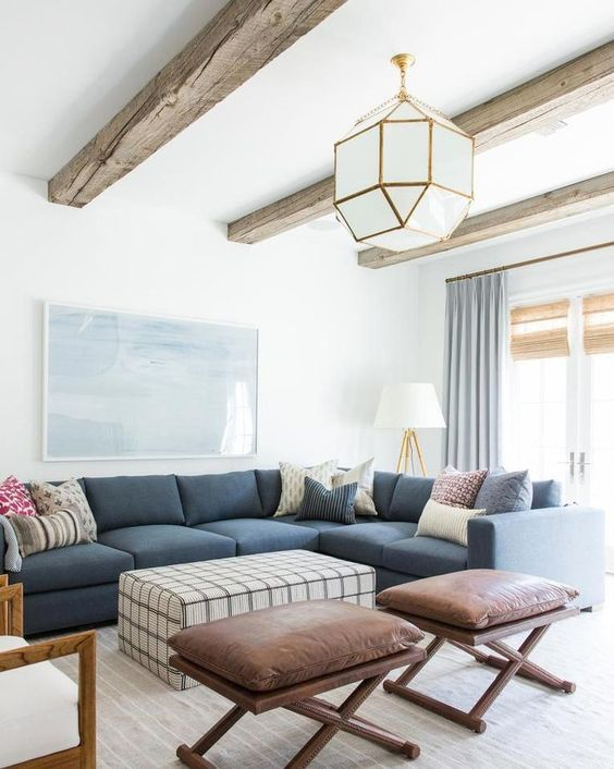 white pendants with golden lines, wooden beam, white wall and ceiling, wooden floor, blue sofa, ottoman for table, leather stool
