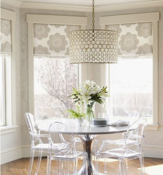 white round dining table, acrylic chairs, beige wall, flower patterned shade, white covered pendant