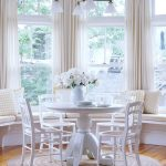 White Round Dining Table, White Wooden Chairs, Wooden Floor, White Ceiling, White Window Bench, Yellow Cushions And Pillows, Beige Curtain, White Chandelier